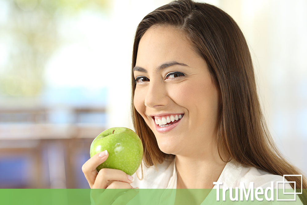 healthy young woman eating apple from Edmonton Naturopath